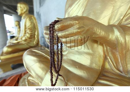 Row of golden seated buddhas in Thailand