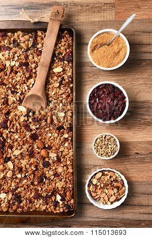 High angle view of fresh homemade granola. Baking sheet filled with the tasty, healthful food with containers of ingredients.