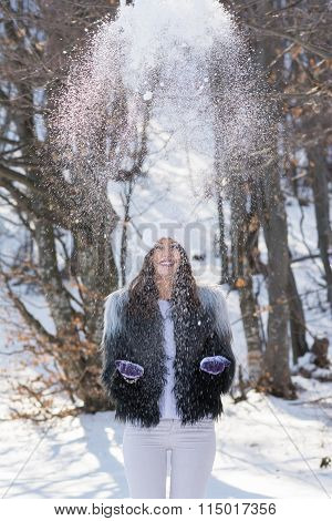 Cheerful young woman playing with snow in park in winter
