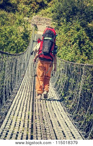 Female hiker crossing a suspension bridge.