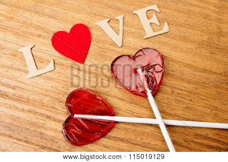 Red heart shaped lollipops on wooden background
