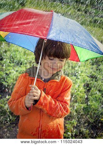 happy boy with umbrella outdoors