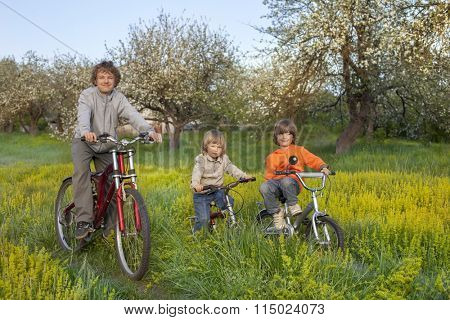 three brothers ride bikes outdoors