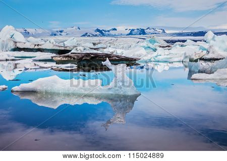 Ice lagoon in July.  Ice floes and icebergs are reflected in the mirrored water of ocean. Summer vacation in Iceland