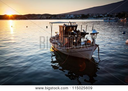 Old fishing boat in harbor at sunset