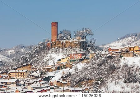 Small village and old medieval tower on background covered with snow in Piedmont, Northern Italy.
