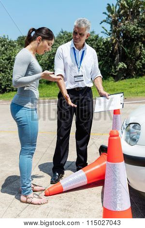 young driving learner running over traffic cones