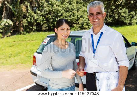 portrait of driving instructor handing driving license to student driver