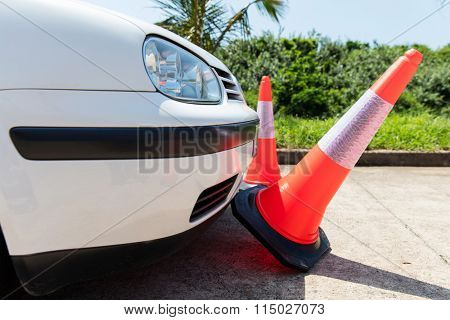 white car bumping the traffic cones