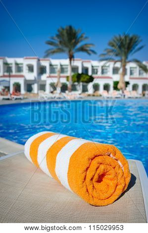 Orange Towel On A Sun Lounger On The Background Of The Pool