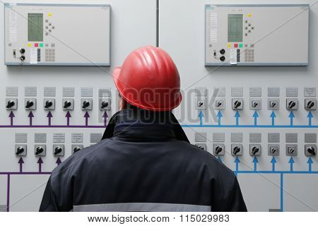 Engineer Reading Instruments In Power Plant Control Center