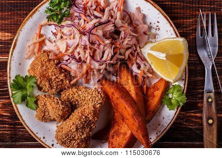 Homemade cooked chicken Nuggets, Sweet Potatoes And Coleslaw.