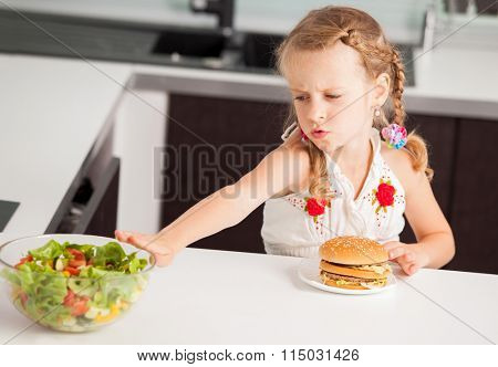 Child chooses between a healthy and unhealthy food. Girl with a hamburger and salad