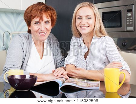 Mother and daughter read magazine at home. Happy women on the kitchen
