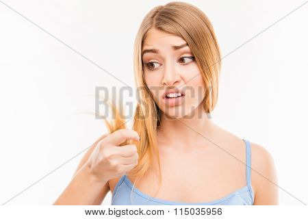 Young Woman Looking At Damaged Split Ends