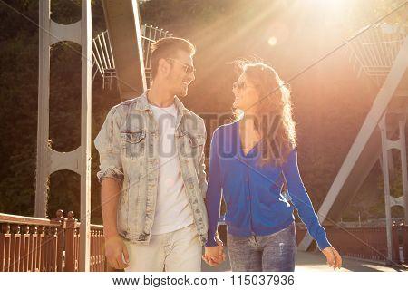 Cheerful Nice Couple In Love On The Bridge Walking Straight