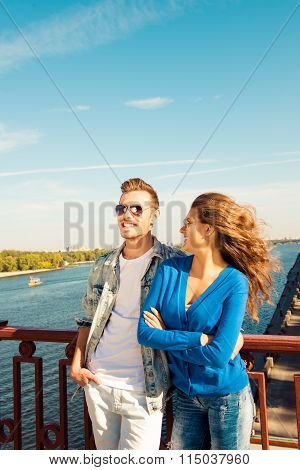 Happy Cute Couple In Love Embracing Each Other On The Bridge