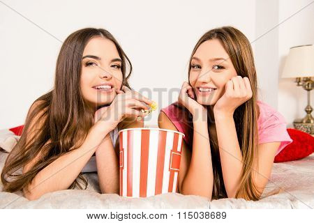 Cheerful Girls In Pajamas Sitting In Plaid With Popcorn