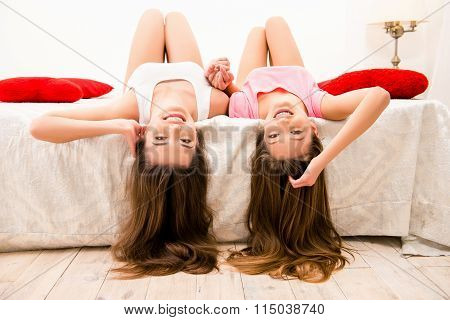 Happy Sexy Girls In Pajamas Lying On The Bed Holding Hands