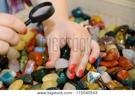 Colorful smooth stones looking through a magnifying glass.