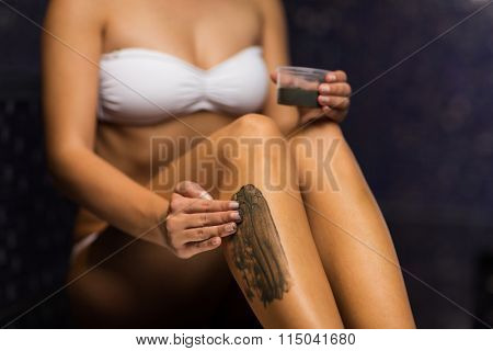 close up of woman applying therapeutic mud in spa