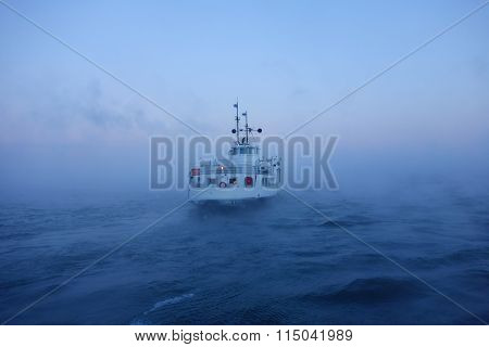 HELSINKI, FINLAND - JANUARY 5: Ferry departing  Suomenlinna fortress island on Baltic sea in midst of thick sea smoke or fog on extremely cold January morning at dawn January 5, 2016 in Helsinki, Finland.