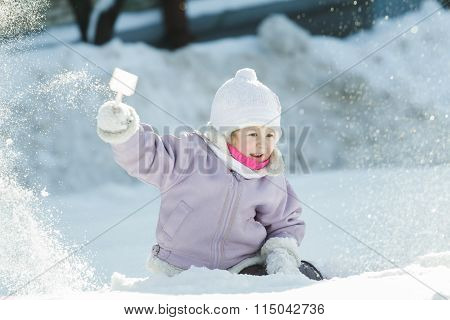 Toddler girl tossing up natural snow with plastic toy shovel in frosty winter sunny day outdoors