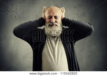 bearded senior man covering his ears and wincing over dark wall