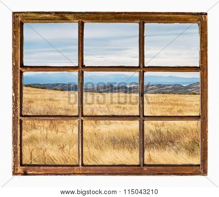 prairie with dry grass at Colorado foothills  as seen  through vintage, grunge, sash window with dirty glass