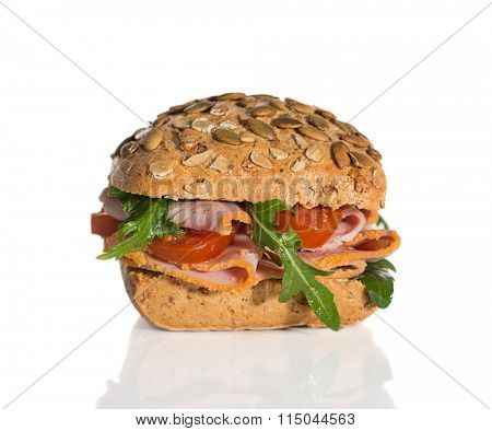 Fresh bread roll filled with ham, tomato and rocket salad