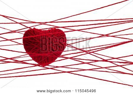 Red heart made from wool isolated on white background