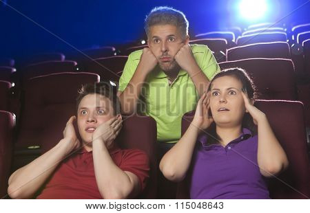 People at the cinema watching an horror movie and screaming