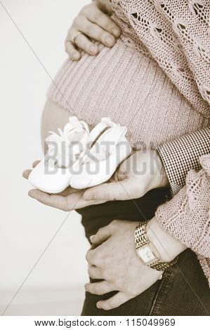 Pregnant woman holding booties from stomach