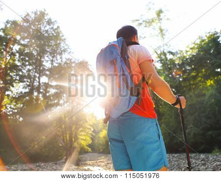 Man Hiking With Backpac And Sticks In Mountains In Sunset