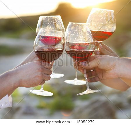 Group Of Friends Toasting Red Wine At A Relax Party Celebration