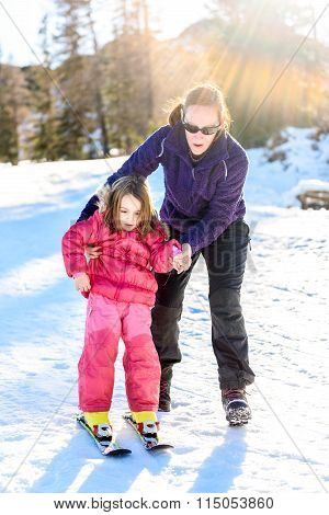 Professional Ski Instructor Is Teaching A Child To Ski On A Sunny Day