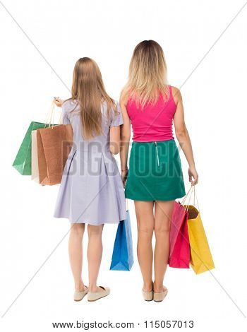 back view of  two women  with shopping bags. backside view of person.  Rear view people collection. Isolated over white background.Young girls in colorful dresses with shopping.