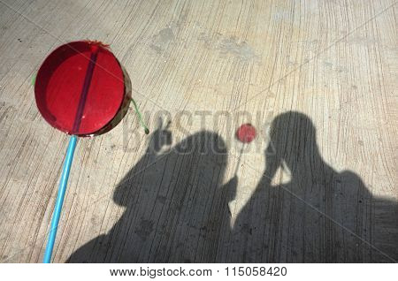 Silhouette of couple playing asian hand drum toy