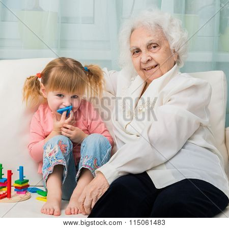 little girl with grandmother sitting on a sofa with toys