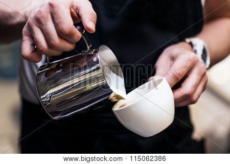 Barista making coffee pouring milk