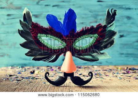 carnival mask ornamented with feathers of different colors and a fake nose and a a fake mustache, on a rustic wooden surface full of confetti