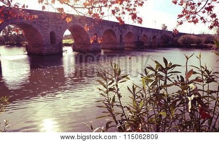 a view of the Puente Romano, an ancient Roman bridge over the Guadiana River, in Merida, Spain, with a filter effect