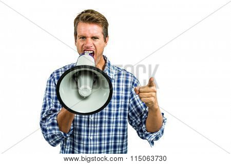 Portrait of angry man yelling through megaphone while standing against white background