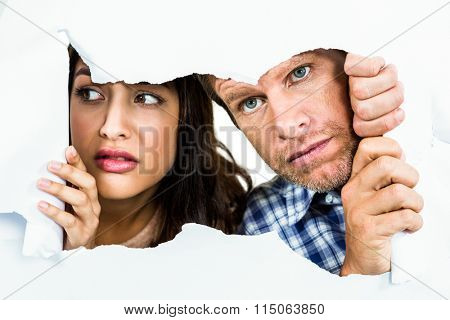 Fearful couple peeking through torn white paper