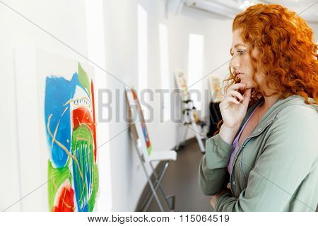 Young caucasian woman standing in art gallery front of  paintings