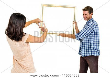 Happy young couple hanging picture frame on white background