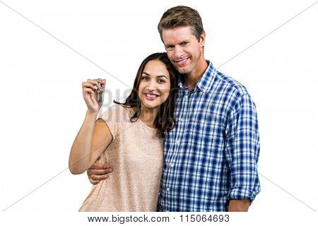 Portrait of happy couple embracing while holding keys against white background