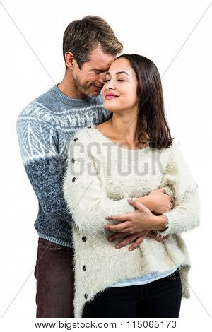 Affectionate couple in warm clothing embracing against white background