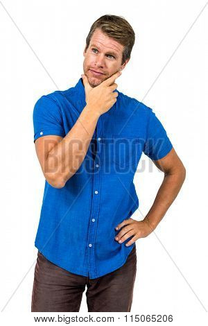Contemplated man with hand on chin standing against white background