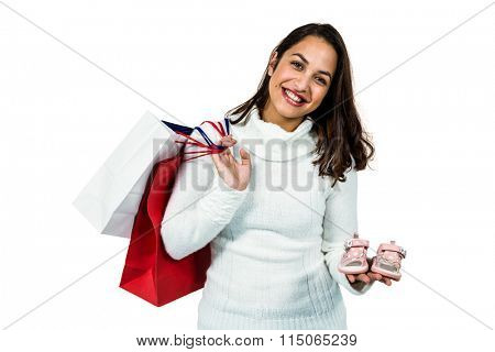 Portrait of happy woman with shopping bags and footwear against white background